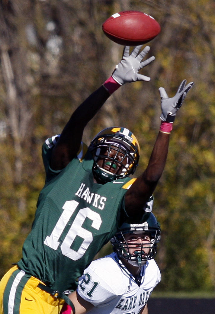 Farmington Hills Harrison defensive back Aaron Burbridge (16)attempts to make an interception as Lake Orion receiver ?? (21) looks on during grid action against Lake Orion at Harrison Saturday.