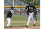 AROUND THE HORN: Lake Orion coach Andy Schramek congradulates Nick Deeg on his way homeafter Deeg blasted a three-run home run during Monday's district finals.  Photo | Larry McKee, www.lmckeephotography.com