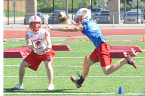 BREAKING UP: Troy Athens senior Joe Shields (right) tries to bat down a pass intended for senior Max Blank during a recent practice. Staff Photo | Dan Stickradt