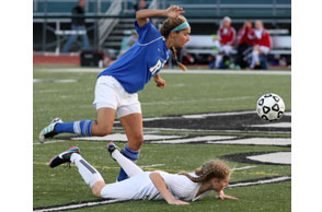 ONE HURDLE AT A TIME: Rochester's Jenna Maletzke leaps over Grand Blanc's Annie Walker during Tuesday's Division 1 regional semifinal. Photo | Larry McKee, www.lmckeephotography.com, lmckeephotography@comcast.net