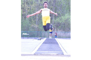 LEAPS AND BOUNDS: Rochester Adams junior Julian McNeir-Sharp flies off the board during the loing jump competition Friday at the Bloomfield Hills Division 1 regional. Staff Photo | Dan stickradt