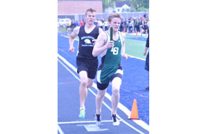 Dropping the anchor: Lake Orion's Kirk Hansen (right) and Ortonville Brandon's Ty Thronson challenge each other in the final lap of the 3,200 relay at Friday's Oakland County Championships. Staff Photo   Dan stickradt